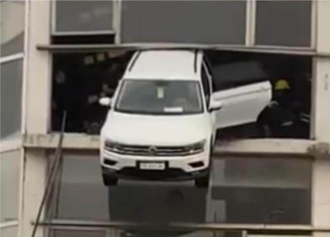 ¡Insólito! Camioneta quedó colgada de una ventana de un concesionario